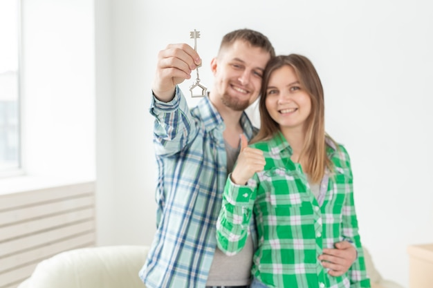 Jong positief paar dat sleutels tot een nieuw appartement houdt terwijl zij in hun woonkamer staan. housewarming en gezinshypotheekconcept.