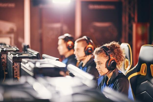 Jong professioneel cybersportteam met koptelefoon die deelneemt aan esport-toernooien, videogames speelt terwijl ze in een gamingclub of internetcafé zitten, focus op een gemengd rasmeisje