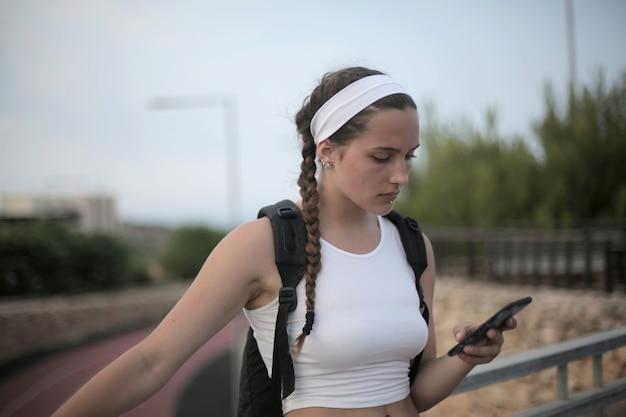 Jong reizend meisje met vlechten en een rugzak die haar telefoon bekijkt