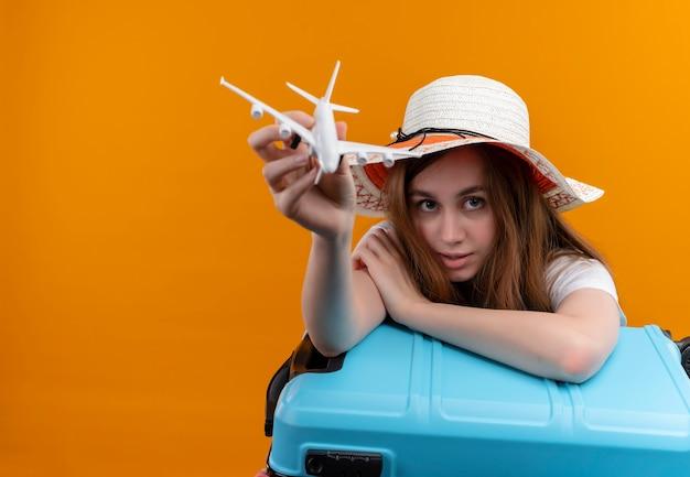 Jong reizigersmeisje dat hoed draagt die modelvliegtuig uitrekt en wapen op koffer op geïsoleerde oranje muur met exemplaarruimte zet