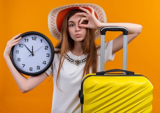 Jong reizigersmeisje dat hoedenkoffer op geïsoleerde oranje muur draagt
