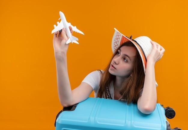 Jong reizigersmeisje die hoed dragen die modelvliegtuig houden en ernaar kijken en arm op koffer zetten en hoed op geïsoleerde oranje muur met exemplaarruimte zetten
