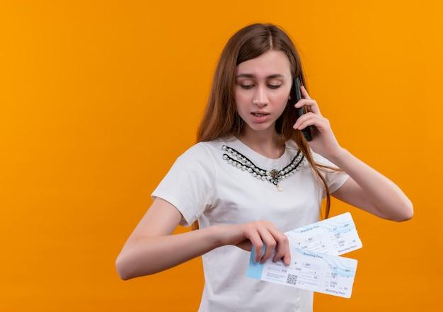 Jong reizigersmeisje die op telefoon spreken en vliegtuigtickets houden die op geïsoleerde oranje muur met exemplaarruimte neerkijken