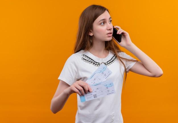 Jong reizigersmeisje die op telefoon spreken en vliegtuigtickets houden die rechterkant op geïsoleerde oranje muur met exemplaarruimte bekijken