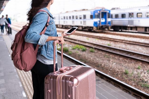 Jong reizigersmeisje in jeansjasje met slimme telefoon, roze zak en bagage die op de trein op het platform wachten, ruimte, reis of vervoersconcept kopiëren