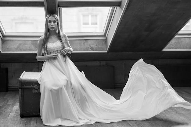 Jong romantisch elegant meisje in lange witte drijvende jurk, zittend op de bruidsschatkist in het hok