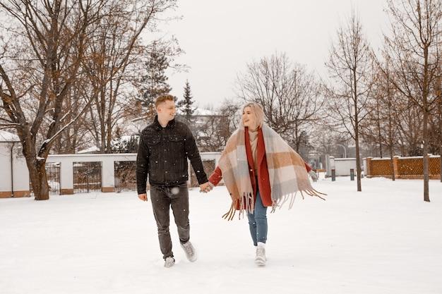 Jong romantisch koppel heeft plezier buiten in de winter. twee geliefden knuffelen en kussen op valentijnsdag.
