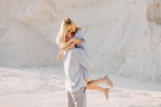 Jong romantisch koppel in het hebben van plezier, buitenshuis. man met vrouw in zijn armen, lachend.