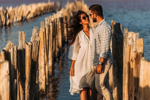 Jong romantisch koppel knuffelen en gaan zoenen in een prachtige zonsondergang. portret van een verliefd stel bij zonsondergang aan zee. mooie verliefde paar genieten van hun huwelijksreis. ruimte kopiëren