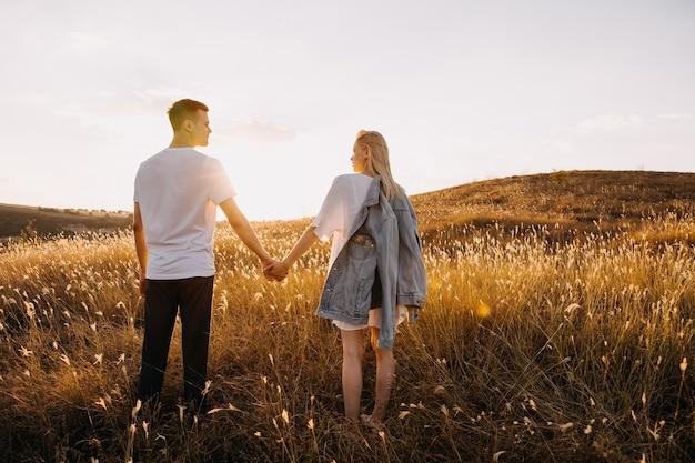 Jong romantisch koppel staande in een open veld met droog gras, hand in hand.