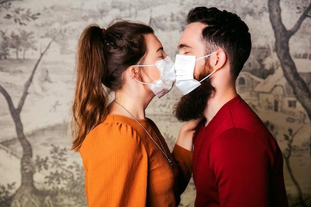 Jong romantisch liefdevol paar dat een beschermend gezichtsmasker voor coronavirus draagt en kussen, boeket bloemen vasthoudt. valentijnsdag en romantiek in het covid-19-concept
