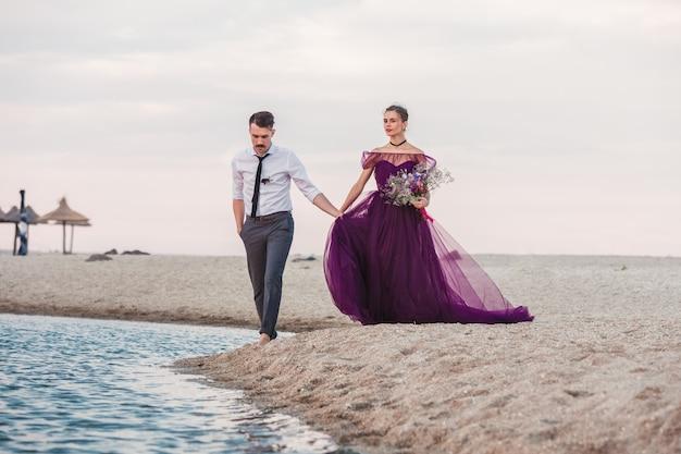 Jong romantisch paar dat op het strand van overzees loopt