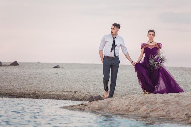 Jong romantische koppel draait op het strand van de zee