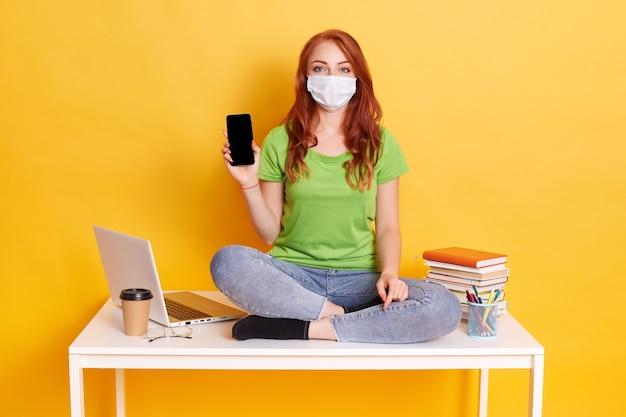 Jong roodharig meisje in ademhalingsmasker met slimme telefoon met leeg scherm, nieuw apparaat aanbevelen, afstandsonderwijs covid quarantaine, zittend op tafel met boeken, laptop, pennen.