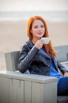 Jong roodharig meisje in blauwe trui met kop die in koffie op het strand in den haag, nederland rust