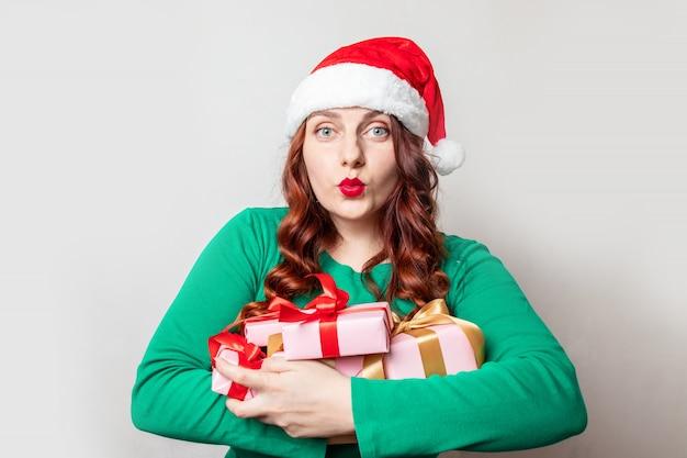 Jong roodharig meisje in een rode kerstmuts en groene trui met veel geschenken zussen in handen