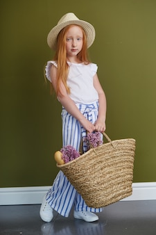 Jong roodharig meisje in een strohoed met lang mooi haar en grote blauwe ogen