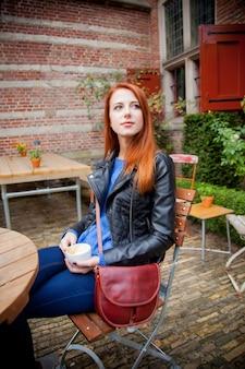 Jong roodharig meisje in hoed in een café in amsterdam, nederland