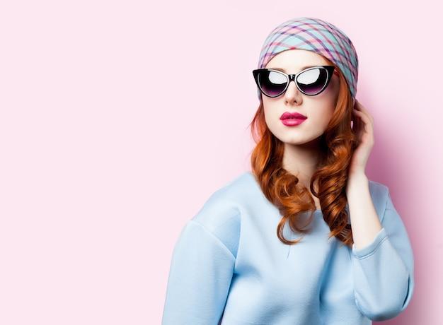 Jong roodharig meisje in mooie blauwe kleren in zonnebril op roze