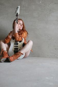 Jong roodharig meisje met elektrische gitaar. rockmuzikant meisje in een leren jas. ze is een mooie zangeres en een performer van rockmuziek.
