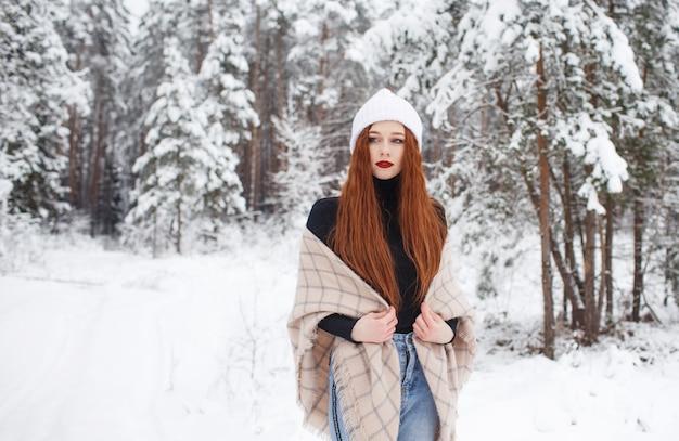 Jong roodharig meisje met lang rood haar op een achtergrond van de winter. roodharige vrouw in een witte hoed op de achtergrond van de winter aard.