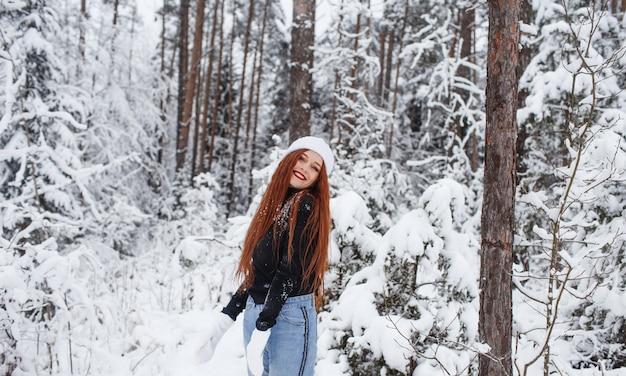 Jong roodharig meisje met lang rood haar op een winterse achtergrond.