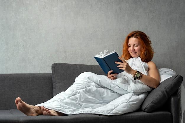 Jong roodharig meisje op de bank onder deken leest boek. gelukkig rustende vrouw.
