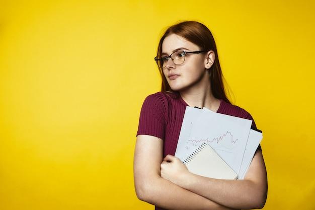 Jong roodharigemeisje die glazen dragen en grafieken en documenten houden