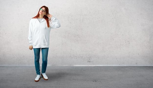 Jong roodharigemeisje in een stedelijk wit sweatshirt met glazen die iets luisteren