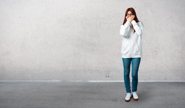 Jong roodharigemeisje in een stedelijk wit sweatshirt met glazen die mond behandelen