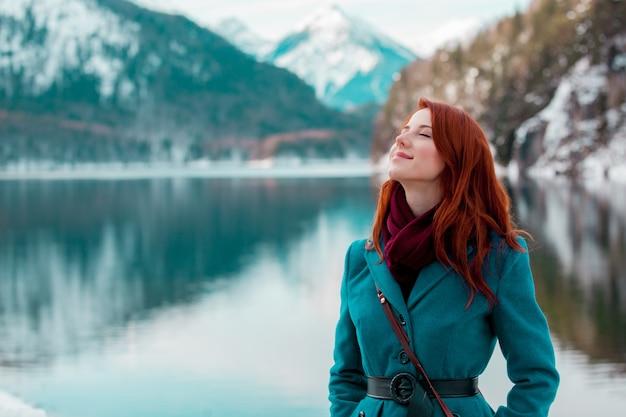 Jong roodharigemeisje in vacht dichtbij meer in alpen, duitsland