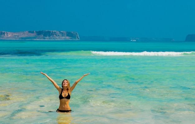 Jong roodharigemeisje in zwarte bikini op balos-strand