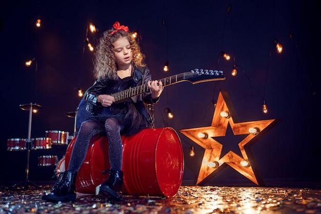 Jong rotsmeisje dat de elektrische gitaar speelt