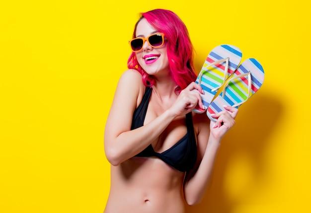 Jong roze haarmeisje in bikini en oranje glazen