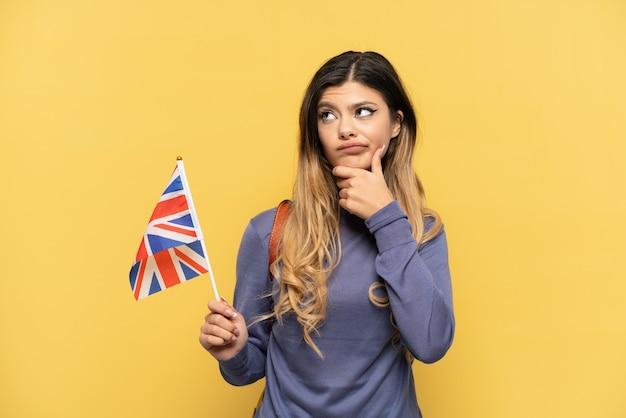 Jong russisch meisje dat een vlag van het verenigd koninkrijk houdt die op gele achtergrond wordt geïsoleerd en een idee denkt