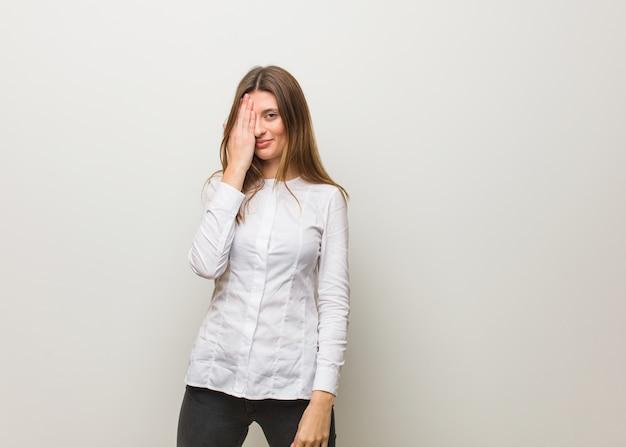 Jong russisch meisje dat gelukkig en kegelvormig gezicht met hand schreeuwt