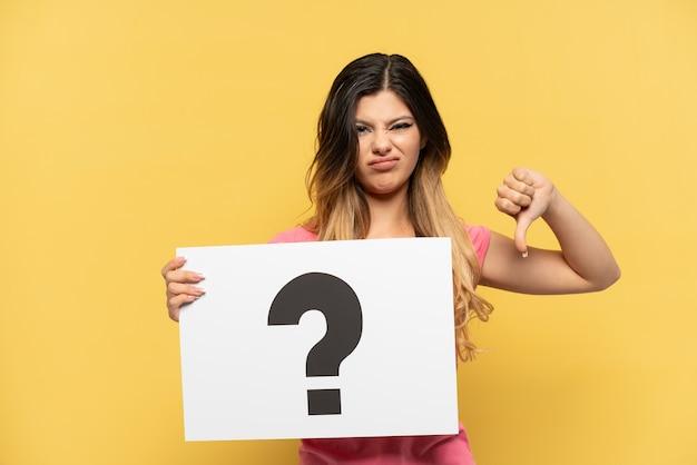 Jong russisch meisje dat op gele achtergrond een plakkaat met vraagtekensymbool houdt en slecht signaal doet