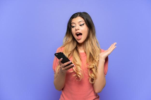 Jong russisch meisje geïsoleerd op blauwe achtergrond kijkend naar de camera tijdens het gebruik van de mobiel met verbaasde uitdrukking