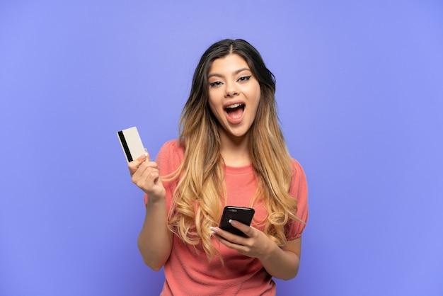 Jong russisch meisje geïsoleerd op blauwe achtergrond kopen met de mobiel en met een creditcard met verbaasde uitdrukking