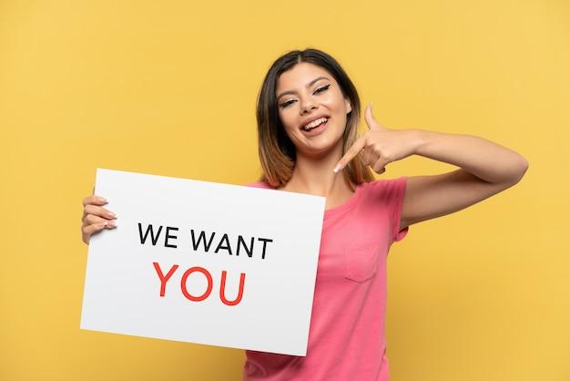 Jong russisch meisje geïsoleerd op een gele achtergrond die we want you aan boord houdt en erop wijst