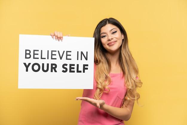Jong russisch meisje geïsoleerd op een gele achtergrond met een bordje met de tekst believe in your self en erop wijzend