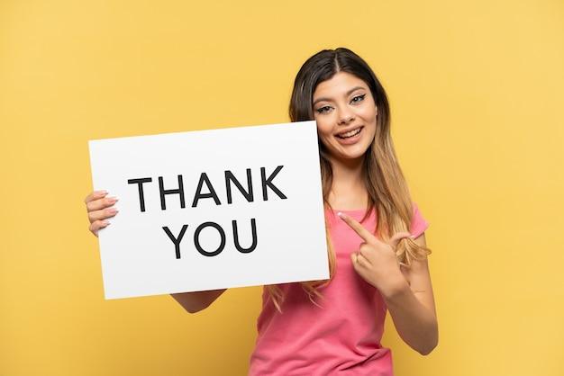 Jong russisch meisje geïsoleerd op een gele achtergrond met een bordje met de tekst dank u en erop wijzend
