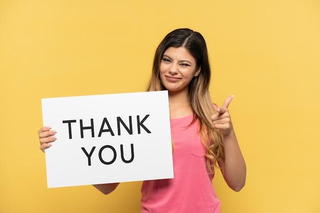Jong russisch meisje geïsoleerd op een gele achtergrond met een bordje met de tekst dank u en naar voren wijzend
