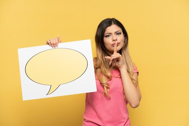 Jong russisch meisje geïsoleerd op een gele achtergrond met een bordje met het pictogram van de toespraakbel die stiltegebaar doet