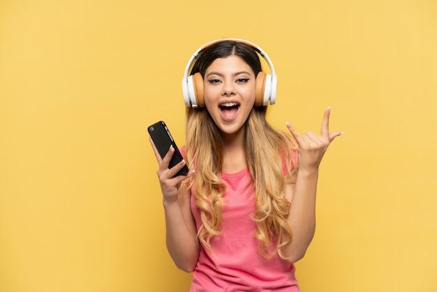 Jong russisch meisje geïsoleerd op gele achtergrond luisteren muziek rock gebaar maken