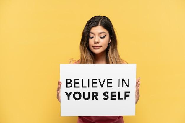 Jong russisch meisje geïsoleerd op gele achtergrond met een bordje met de tekst believe in your self