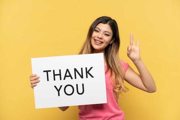 Jong russisch meisje geïsoleerd op gele achtergrond met een bordje met de tekst dank u met ok teken