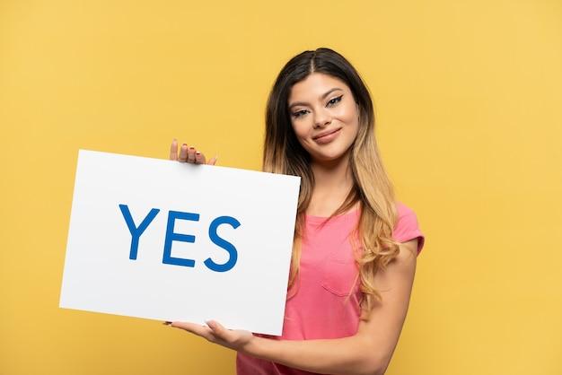 Jong russisch meisje geïsoleerd op gele achtergrond met een bordje met de tekst ja met gelukkige uitdrukking
