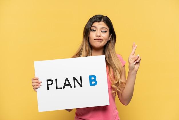Jong russisch meisje geïsoleerd op gele achtergrond met een bordje met het bericht plan b met vingers over elkaar