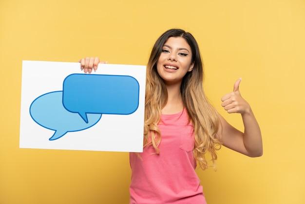 Jong russisch meisje geïsoleerd op gele achtergrond met een bordje met tekstballon pictogram met duim omhoog
